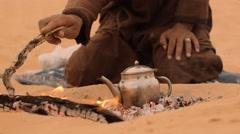 Man preparing tea in the desert, close up Stock Footage