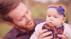 A young man playing with his baby daughter under a gazebo Stock Footage