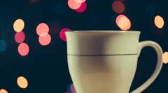 Hot beverage in the cup rotate around its axis on bokeh background Stock Footage