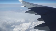 Passenger aircraft wing against distant mountains Stock Footage