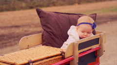 A baby being pulled in a wagon at a pumpkin patch on a fall day Stock Footage