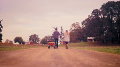 A couple holding hands while pulling a wagon at a pumpkin patch Stock Footage
