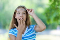 teenage girl with her hand covers mouth in amazement - stock photo