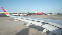 Airliner taxiing off at Thai airport, Hat Yai city. Wing view from porthole - stock footage