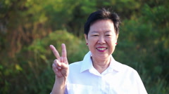 Asian senior woman thumb up and smiling with green nature background Stock Footage