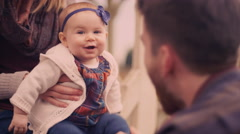 Man playing with his baby daughter while her mother holds her on her lap Stock Footage