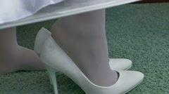 Bride puts shoes on his feet detail of wedding fees Stock Footage