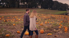 A young couple carrying their baby around at a pumpkin patch Stock Footage
