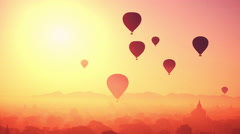 Hot air balloons flying at sunrise over Buddhist Temples at Bagan. Myanmar Stock Footage