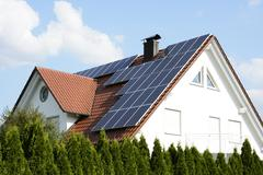 Green energy with solar panels on the roof of a modern house. Kuvituskuvat