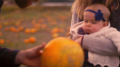 A man showing a pumpkin to his baby girl at the pumpkin patch Stock Footage