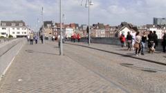 People walk by the medieval Saint Servatius bridge in Maastricht, Netherlands. Stock Footage