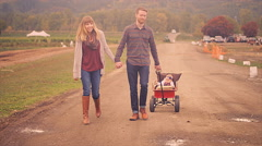 A couple walking and holding hands while pulling their baby in a wagon Stock Footage