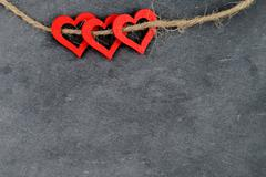 Vintage chalkboard with three red heart shape symbols on rope,  retro filter  Stock Photos