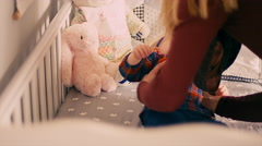 A mother picks her crying baby girl up out of her crib Stock Footage