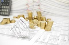 Bankruptcy of house with gold coins fall to the ground - stock photo