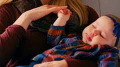 A mother rocking her baby to sleep in a rocking chair in a nursery Stock Footage