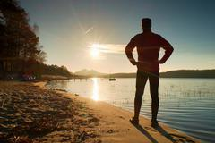 Silhouette of tall sportsman on decline seeing over bay to sun Stock Photos