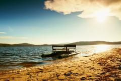 Abandoned old rusty paddle boat stuck on sand of beach. Wavy water level, isl Stock Photos