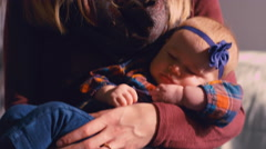 A baby being bounced to sleep by her mother on a yoga ball in a nursery Stock Footage
