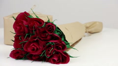 Maroon paper roses and a gift box Stock Footage