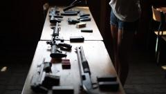 Table full of firearms arsenal cute girl reloading gun Stock Footage