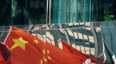 Flags Reflection of Hong Kong and China and skyscrapers tilting shot. - stock footage