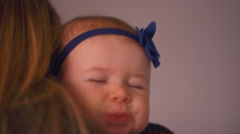 Close up of a fussy baby falling asleep on her mother's shoulder Stock Footage