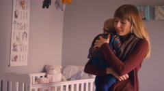 A mother holding her baby trying to get her to fall asleep Stock Footage