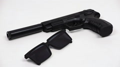 Gun with a silencer and black glasses Stock Footage