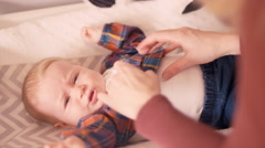 A mother dressing her baby on a changing table in a nursery Stock Footage
