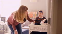 A young mother standing next to her baby sitting on a changing table Stock Footage