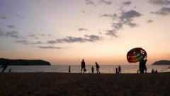 People figures on sunset beach, parakite canopy start and fly, time lapse - stock footage
