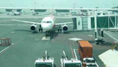 Aircraft approach and stop at apron, jet bridge attached, time lapse shot Stock Footage