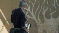 Man practising saxophone under bridge,Battambang,Cambodia Stock Footage