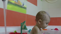 Small child the age of one year plays and jumps in the bathroom. Slow motion Stock Footage