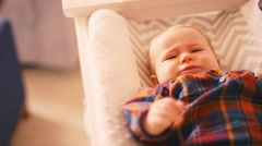 An upset baby laying on a changing table after being dressed Stock Footage