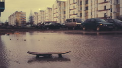 Old skateboard in a dirty puddle on a multi storey building and cars background Stock Footage