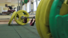 Closeup barbell, athlete puts the barbell plates to the bar to the fore Stock Footage