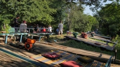 Tourists arriving on Bamboo train station in norry,Battambang,Cambodia Stock Footage