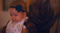 Close up of a baby wearing a bib sitting on her mother's lap at home Stock Footage