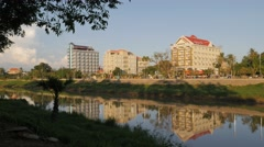 Sanker river with reflection of big hotels,Battambang,Cambodia Stock Footage