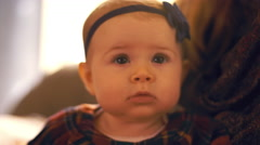 Close up of a baby sitting on her mother's lap at home Stock Footage