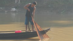 Fisher man pulling net in canoe,Battambang,Cambodia Stock Footage