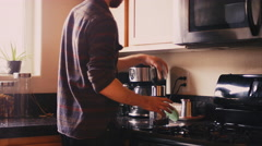 A young man pouring coffee beans into a coffee grinder in his kitchen Stock Footage