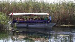 People sitting in a boat travel in river water. Akyaka, Turkey Stock Footage