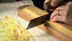 cutting italian Pasta -tagliatelle- with old knife on and wooden table - stock footage