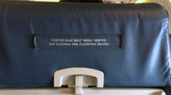 Fasten Seat belt while seated sign on back of airplane chair 4k Stock Footage