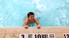 Young boy playing and splashing in swimming pool 4k - stock footage