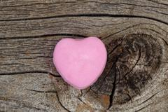 Happy Valentines day with single pink heart shaped candy on rustic wood Stock Photos